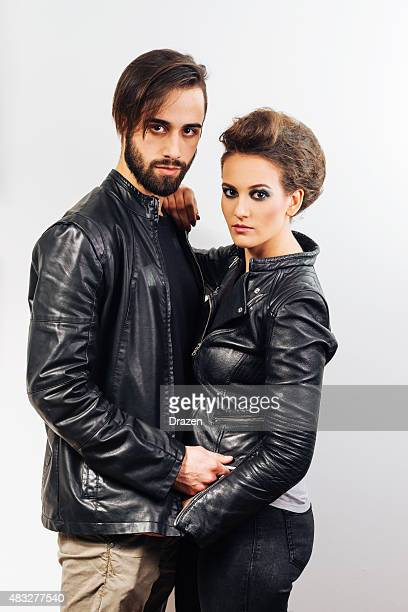 Heterosexual young modern couple posing in black leather jackets