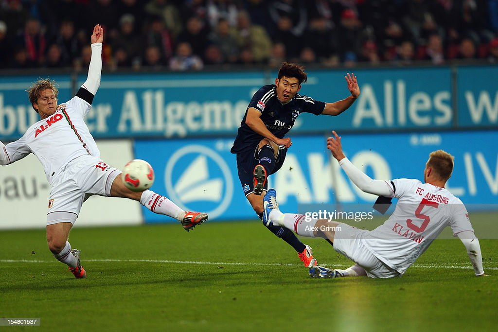 Heung-Min Son (C) of Hamburg scores his team's first goal against Marcel de Jong (L) and Ragnar Klavan of Augsburg during the Bundesliga match between FC Augsburg and Hamburger SV at SGL Arena on October 26, 2012 in Augsburg, Germany.