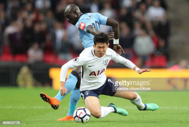 HeungMin Son of Tottenham goes down under pressure from Mohamed Diame of Newcastle during the Premier League match between Tottenham Hotspur and...