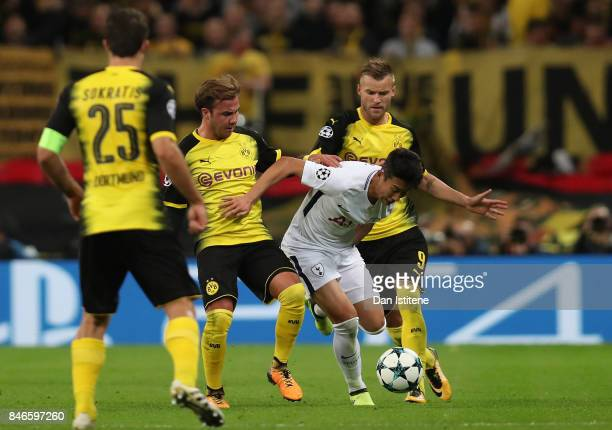 HeungMin Son of Tottenham Hotspur and Mario Gotze of Borussia Dortmund battle for possession during the UEFA Champions League group H match between...
