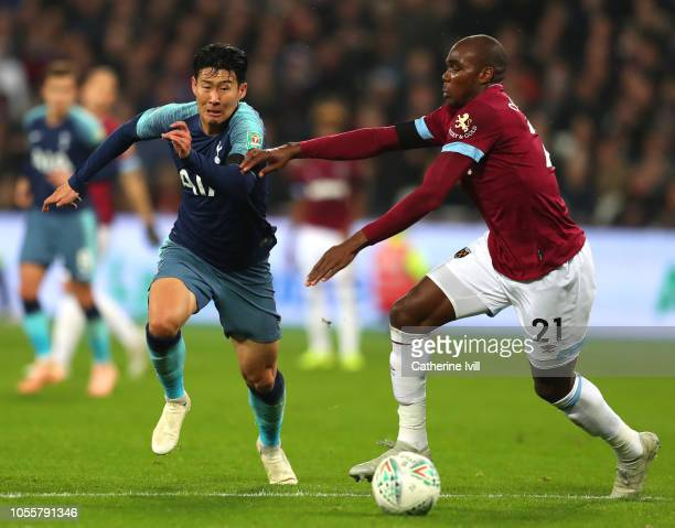 HeungMin Son of Tottenham Hotspur battles for possession with Angelo Ogbonna of West Ham United during the Carabao Cup Fourth Round match between...