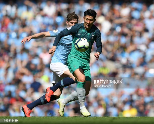 HeungMin Son of Tottenham Hotspur battles for possession with John Stones of Manchester City during the Premier League match between Manchester City...
