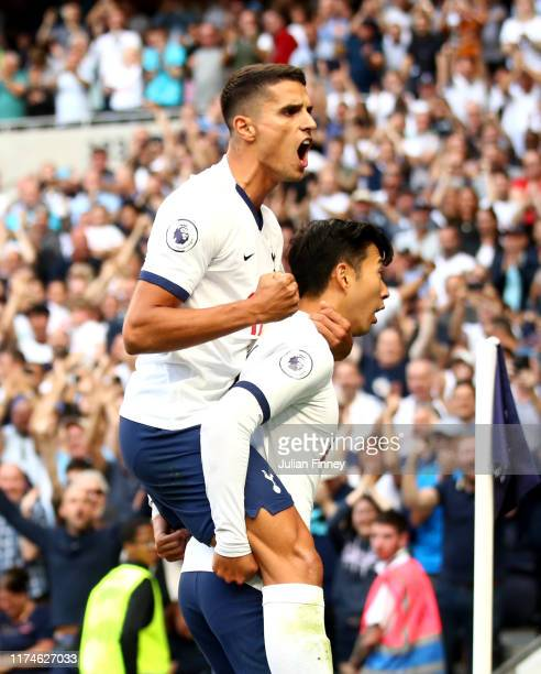 HeungMin Son of Tottenham Hotspur celebrates with teammate Erik Lamela after scoring his team's first goal during the Premier League match between...