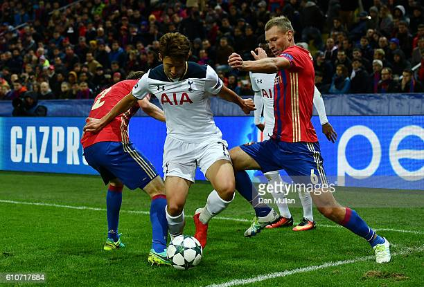 HeungMin Son of Tottenham Hotspur holds off Aleksey Berezutskiy and Mario Fernandes of CSKA Moscow during the UEFA Champions League Group E match...
