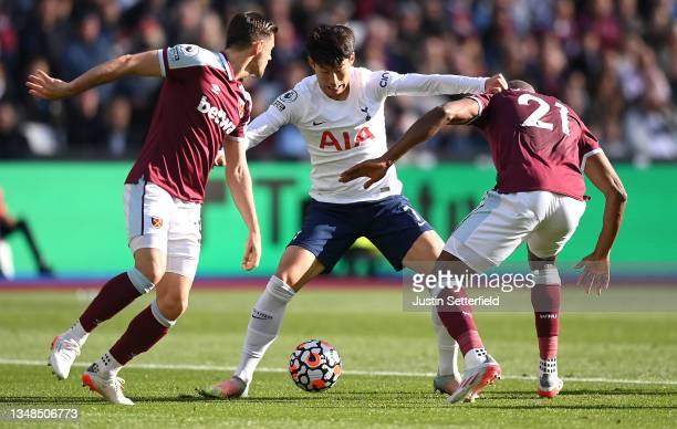 Heung-Min Son of Tottenham Hotspur holds off Angelo Ogbonna and Aaron Cresswell of West Ham United during the Premier League match between West Ham...