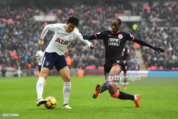 HeungMin Son of Tottenham Hotspur is blocked by Terence Kongolo of Huddersfield Town during the Premier League match between Tottenham Hotspur and...