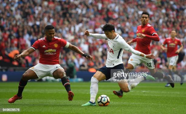 HeungMin Son of Tottenham Hotspur is challenged by Antonio Valencia of Manchester United during The Emirates FA Cup Semi Final match between...