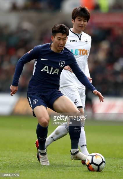 HeungMin Son of Tottenham Hotspur on the ball under pressure from Ki SungYueng of Swansea City during The Emirates FA Cup Quarter Final match between...