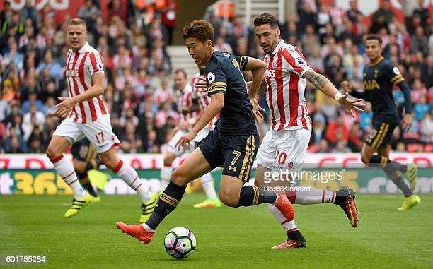 HeungMin Son of Tottenham Hotspur on the ball while under pressure Geoff Cameron of Stoke City during the Premier League match between Stoke City and...