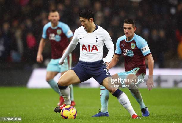 HeungMin Son of Tottenham Hotspur runs with the ball under pressure from Ashley Westwood of Burnley during the Premier League match between Tottenham...