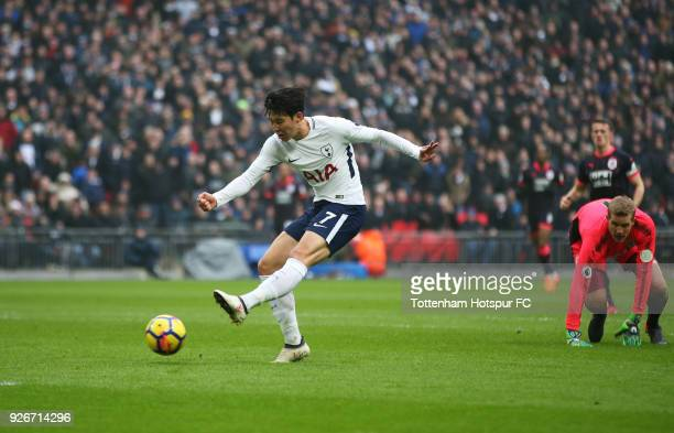 HeungMin Son of Tottenham Hotspur scores their first goal as Jonas Loessl of Huddersfield Town looks on during the Premier League match between...