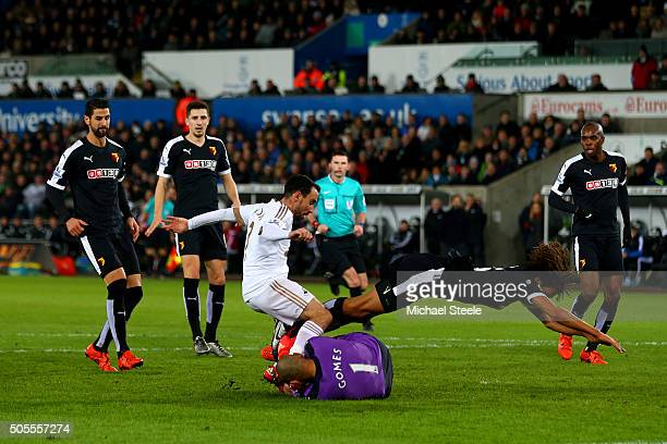 Heurelho Gomes of Watford collects the ball at the feet of Leon Britton of Swansea City as Nathan Ake of Watford tumbles during the Barclays Premier...