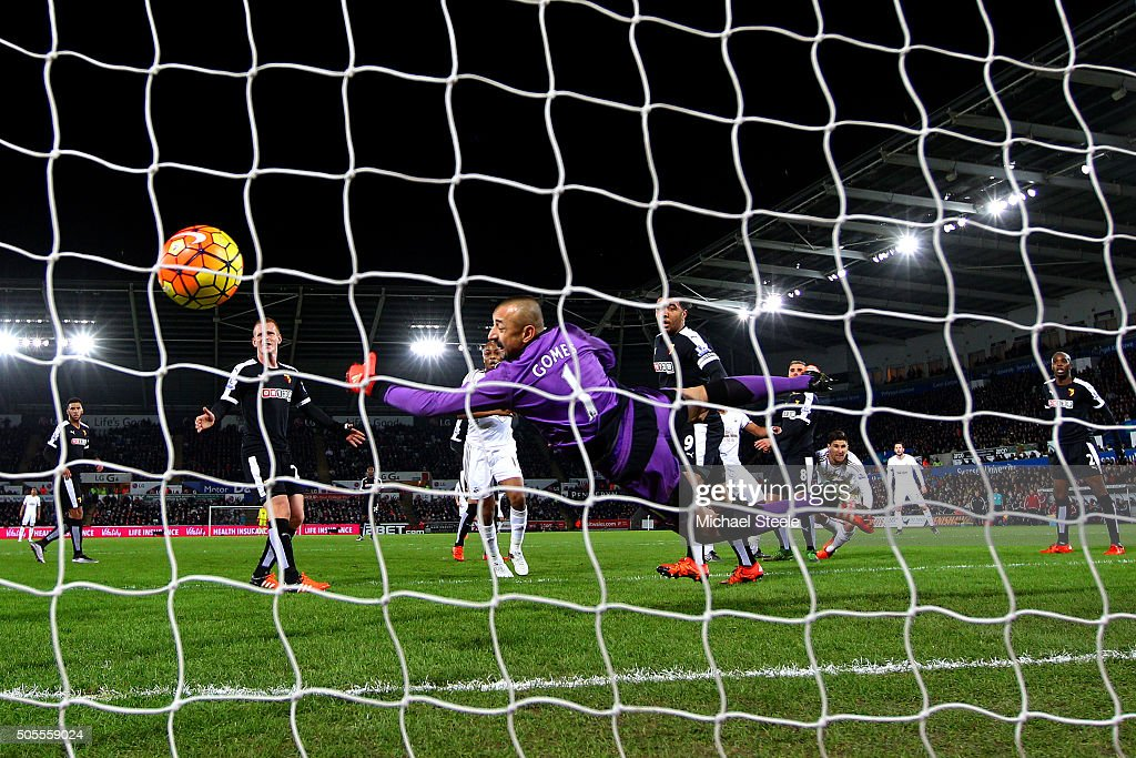 Heurelho Gomes of Watford dives in vain as Ashley Williams (hidden) of Swansea City scores the opening goal during the Barclays Premier League match between Swansea City and Watford at Liberty Stadium on January 18, 2016 in Swansea, Wales.