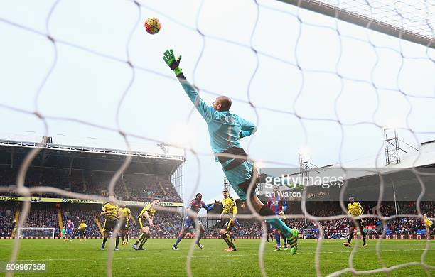 Heurelho Gomes of Watford dives in vain as Emmanuel Adebayor of Crystal Palace scores his team's first goal during the Barclays Premier League match...