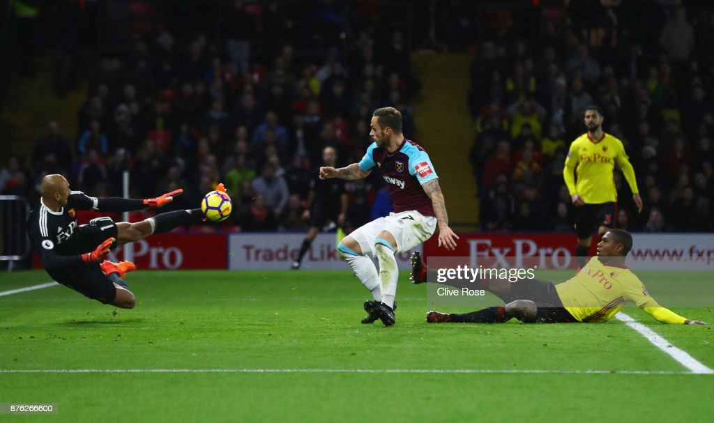 Heurelho Gomes of Watford makes a save from Marko Arnautovic of West Ham United (C) during the Premier League match between Watford and West Ham United at Vicarage Road on November 19, 2017 in Watford, England.