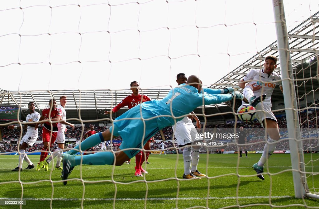 Heurelho Gomes of Watford saves a shot from Federico Fernandez of Swansea City during the Premier League match between Swansea City and Watford at Liberty Stadium on September 23, 2017 in Swansea, Wales.