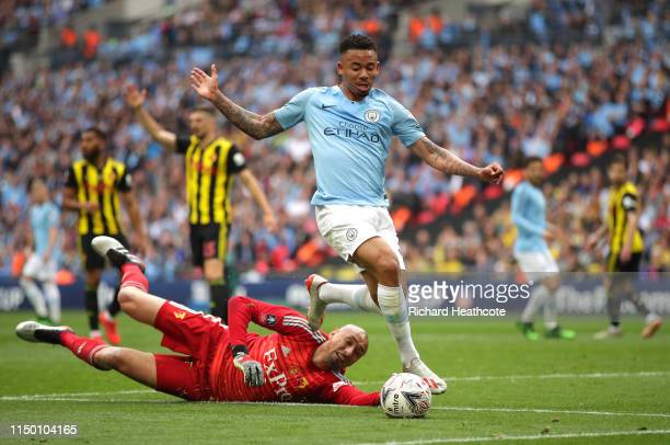 Heurelho Gomes of Watford stretches for the ball under pressure from Gabriel Jesus of Manchester City during the FA Cup Final match between...