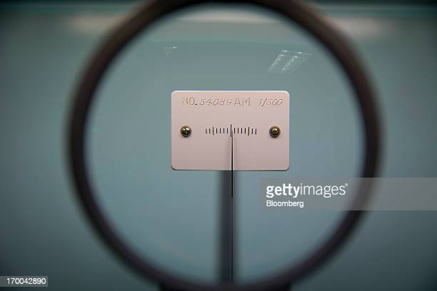 A Heusser scale used for weighing gold is seen through a magnifying glass as it sits on a laboratory counter at the United States Mint at West Point...