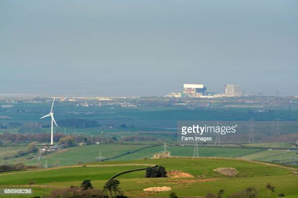 Heysham nuclear power station and a wind powered turbine in the countryside Lancashire UK