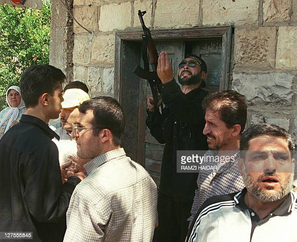 A Hezbollah fighter welding a Kalashnikov AK47 assault rifle speaks to villagers in Marqaba 22 May 2000 after Israel's proxy South Lebanon Army...