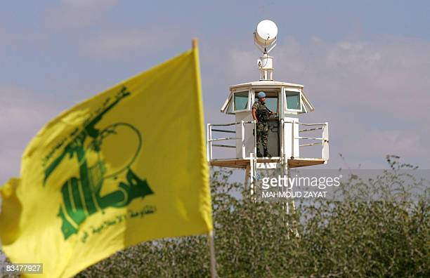 A Hezbollah flag flies in the foreground as a member of the Spanish contingent of the United Nations Interim Force in Lebanon stands in a lookout...