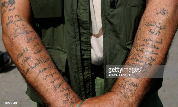A Hezbollah militant his arms sporting tattoos of names of his dead comrades takes part in the funeral procession of a Hezbollah militant in the Uzai...