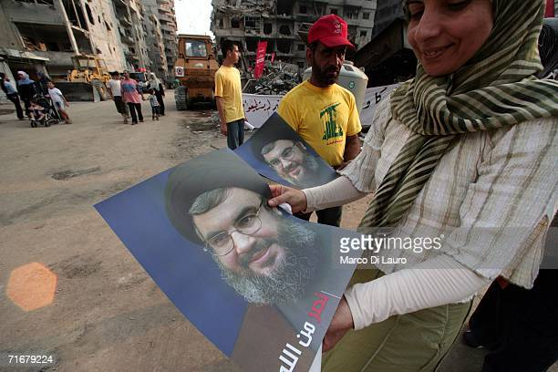Hezbollah supporter passes out a poster of Hezbollah leader Hassan Nasrallah August 19 2006 in the southern suburb of Haret Hreik in Beirut Lebanon...