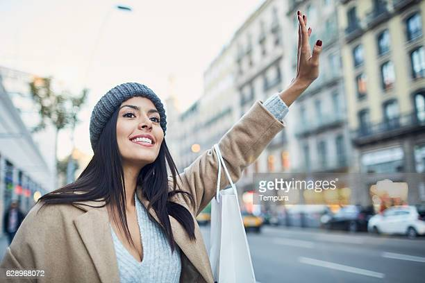 hialing a taxi after some christmas shopping. - hail stock photos and pictures