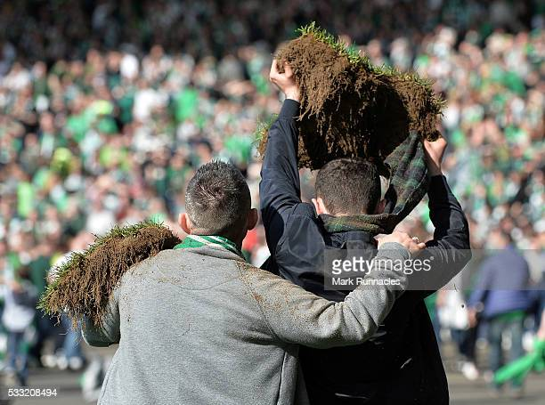 Hibernian fan walks from the pitch with a piece of the Hamden Park playing surface after a pitch invasion at the final whistle as Hibernian beat...