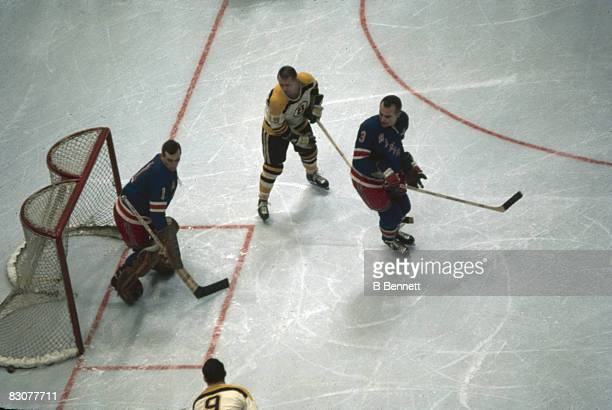 Hich angle view of Canadian ice hockey player Ed Giacomin goalkeeper for the New York Rangers as he and teammate Harry Howell try to fend off an...