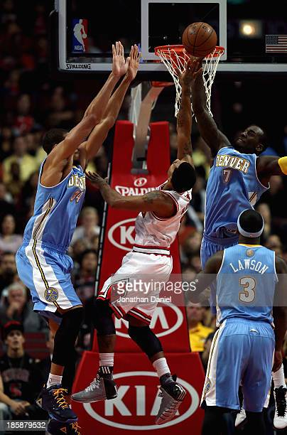 J Hickson of the Denver Nuggets blocks a shot by Derrick Rose of the Chicago Bulls as JaVale McGee defends during a preseason game at the United...