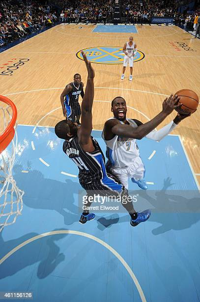 J Hickson of the Denver Nuggets goes to the basket against Andrew Nicholson of the Orlando Magic on January 7 2015 at the Pepsi Center in Denver...
