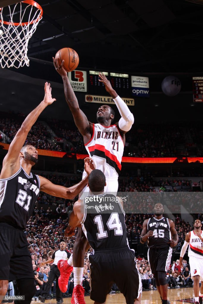 J.J. Hickson #21 of the Portland Trail Blazers drives to the basket and puts up a shot over Tim Duncan #21 of the San Antonio Spurs on December 13, 2012 at the Rose Garden Arena in Portland, Oregon.