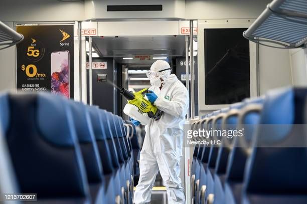 A Long Island Rail Road employee disinfects a train car with an ecofriendly cleaner while at the Hicksville New York LIRR station on March 19 2020