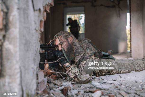 hidden soldier with rifle sniper in building. - military invasion stock pictures, royalty-free photos & images