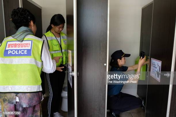 A hiddencamera search squad consisting of student and citizen volunteers scan a restroom near a public pool in Changwon South Korea on July 25 2018