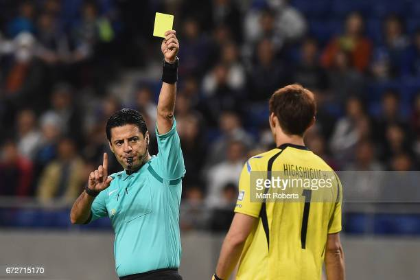 Hideaki Higashiguchi of Gamba Osaka is give a yellow card by the referee during the AFC Champions League Group H match between Gamba Osaka v Adelaide...