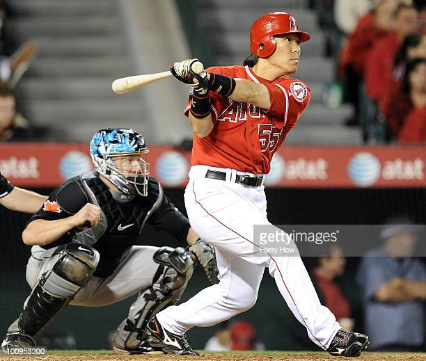 Hideki Matsui of the Los Angeles Angels hits a single in front of John Buck of the Toronto Blue Jays during the seventh inning at Angel Stadium on...