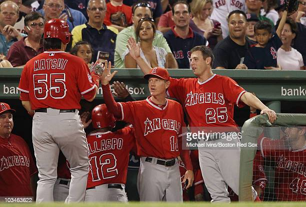 Hideki Matsui of the Los Angeles Angels of Anaheim is congratulated by teammates Ron Roenicke and Peter Bourjos after Matsui hit a three run homer in...