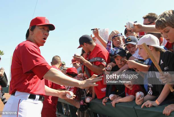 Hideki Matsui of the Los Angeles Angels of Anaheim reacts as the fence holding back fans breaks before the MLB spring training game against the...