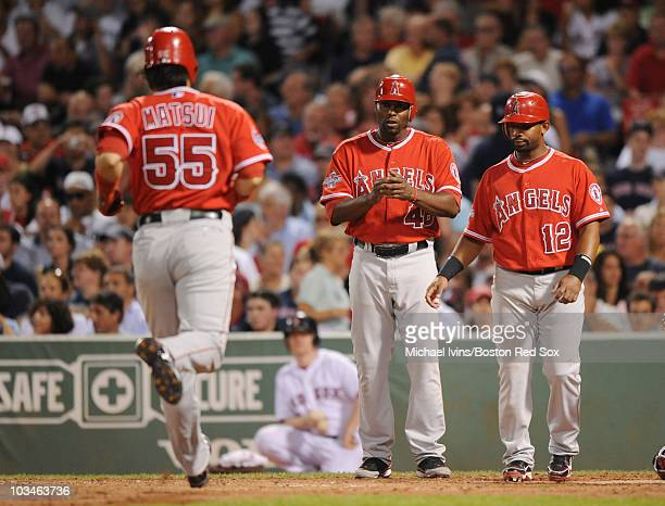 Hideki Matsui of the Los Angeles Angels of Anaheim trots to home plate to be greeted by Torii Hunter and Alberto Callaspo after hitting a threerun...