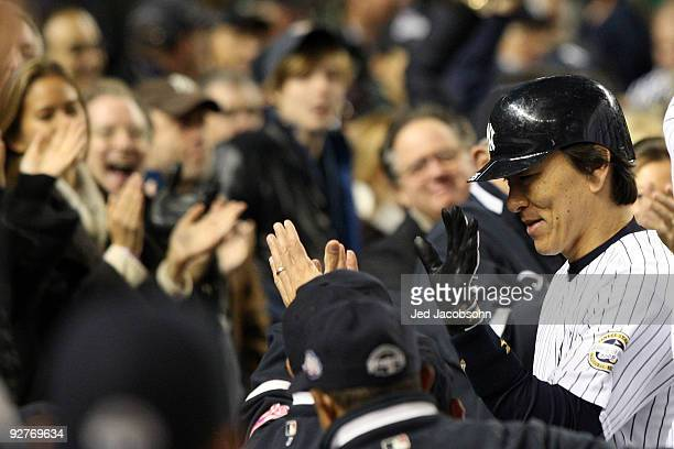 Hideki Matsui of the New York Yankees celebrates with his teammates in the dugout after he hit a 2run home run in the bottom of the second inning...