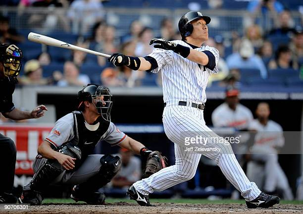Hideki Matsui of the New York Yankees hits a threerun home run in front of Chad Moeller of the Baltimore Orioles in the eighth inning of a game at...