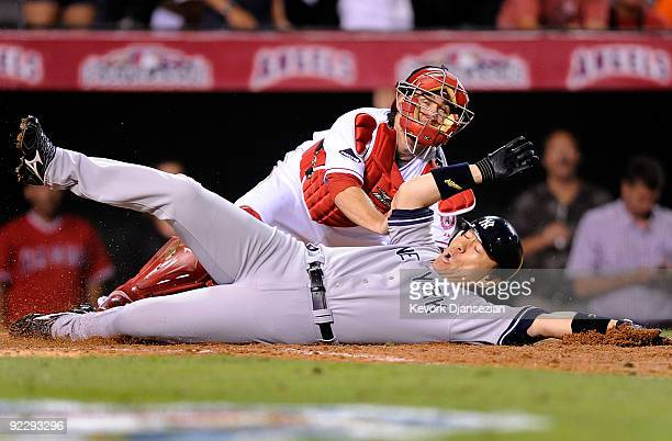 Hideki Matsui of the New York Yankees slides into home base safe ahead of Jeff Mathis of the Los Angeles Angels of Anaheim tag during the seventh...