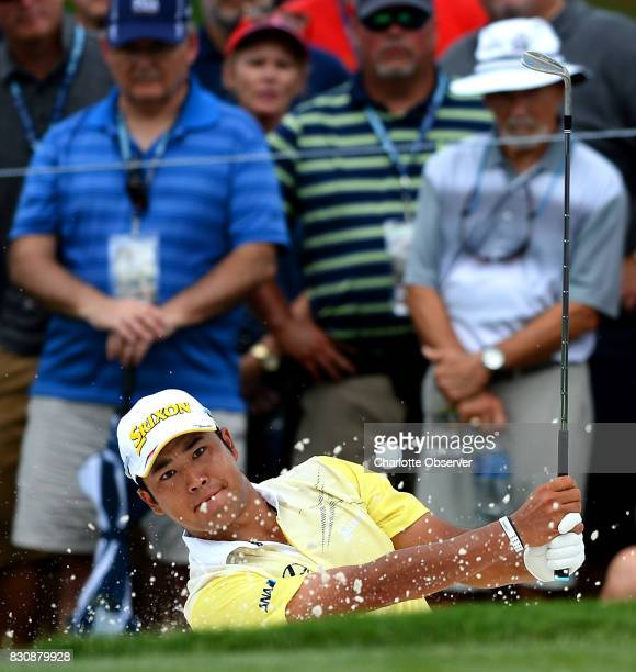 Hideki Matsuyama chips out of a sand trap along the 1st green in the third round of the PGA Championship at Quail Hollow Club in Charlotte NC on...