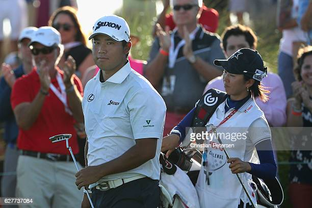 Hideki Matsuyama of Japan and caddie Mei Inui react after chipping onto the 18th green during the final round of the Hero World Challenge at Albany...