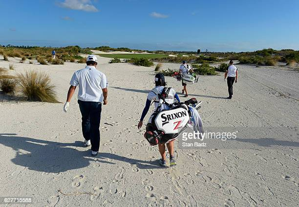 Hideki Matsuyama of Japan and caddie Mei Inui walk along the 16th hole during the final round of the Hero World Challenge at Albany course on...