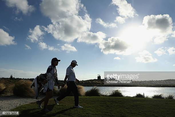 Hideki Matsuyama of Japan and caddie Mei Inui walk down the 17th hole during the final round of the Hero World Challenge at Albany The Bahamas on...