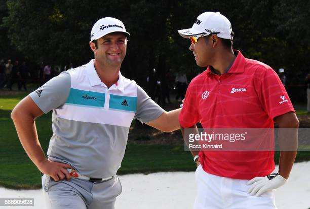 Hideki Matsuyama of Japan and Jon Rahm of Spain react after their balls landed touching in a bunker on the 18th hole during the second round of the...