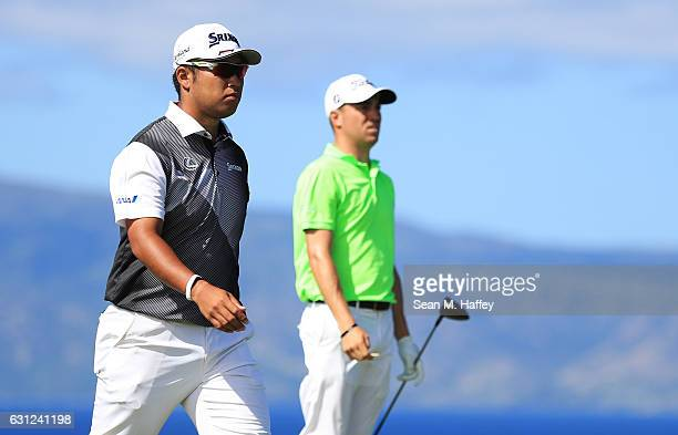 Hideki Matsuyama of Japan and Justin Thomas of the United States walk from the 13th tee during the final round of the SBS Tournament of Champions at...